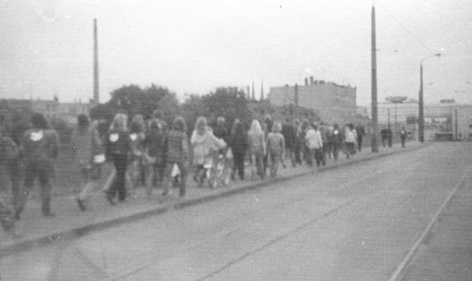 Der erste September ist im DDR-Kalender als Weltfriedenstag gekennzeichnet. Am späten Nachmittag dieses Sommertages 1982 versammelt sich die OA auf der Peißnitz-Insel. Die Staatssicherheit dokumentiert aufwendig Anwesenheiten und Aktivitäten. Mit dem Symbol der Friedenstaube von Pablo Picasso auf der Schulter macht sich die OA am frühen Abend auf ihren Weg durch die Mansfelder Straße zur Marktkirche. Die staatlichen Stellen schätzen das als Demonstrativverhalten ein. Deutlich wird, dass der Operativvorgang Prävention ein hohes Risiko birgt: Was, wenn öffentlichkeitswirksame Aktionen des Jugenddiakons und der OA nicht effektiv verhindern werden können?  Die OA auf dem Weg in die Altstadt (Foto: unbekannt / Privatbesitz Lothar Rochau).